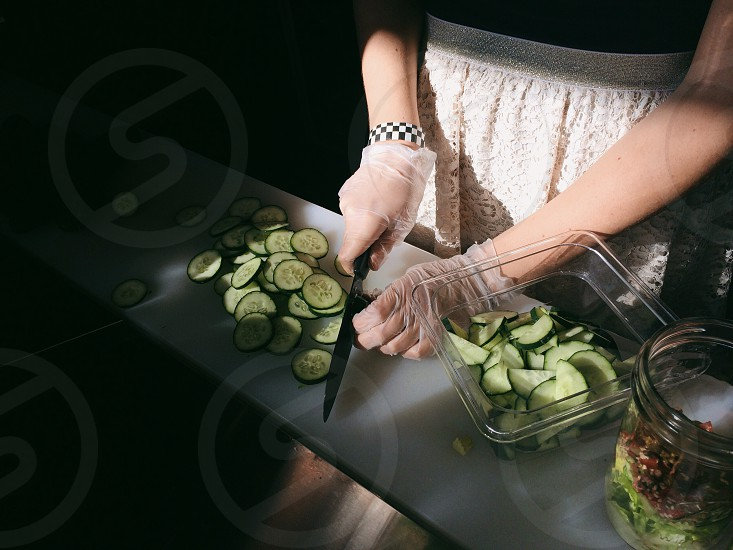 woman wearing a white skirt slicing cucumbers photo