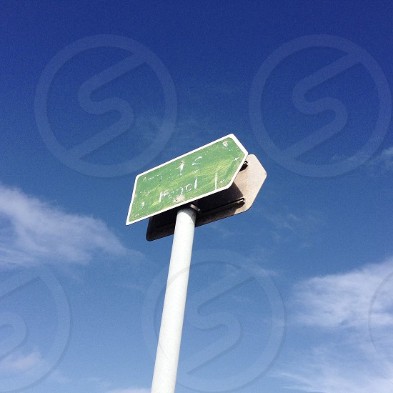 Green road sign with blue sky. photo