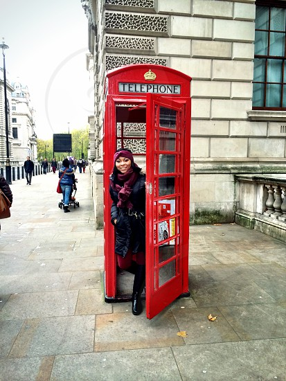 woman in a red telephone booth photo