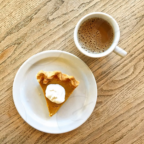 Pie and coffee on a wooden tabletop.  photo