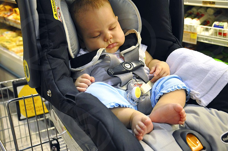 Newborn baby girl sleeping in a car seat while grocery shopping.  photo