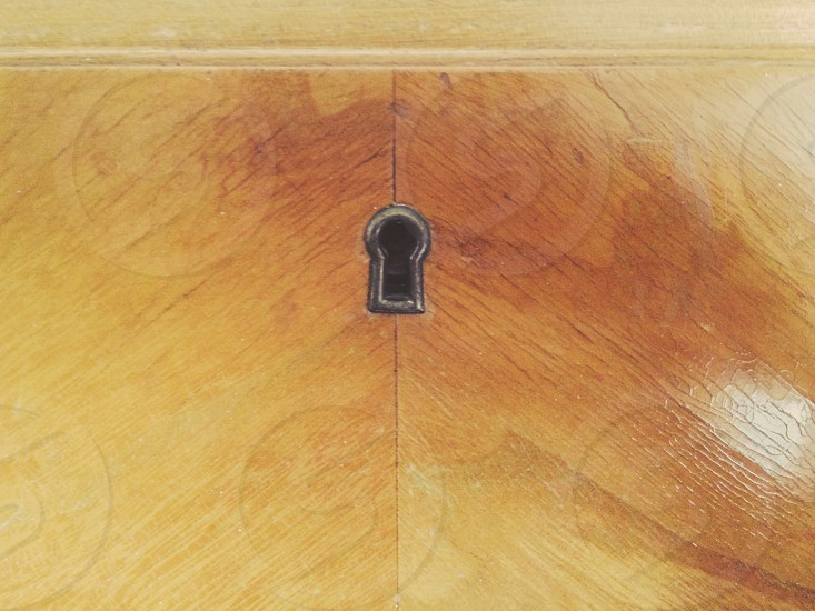 silver keyhole on brown wood photo