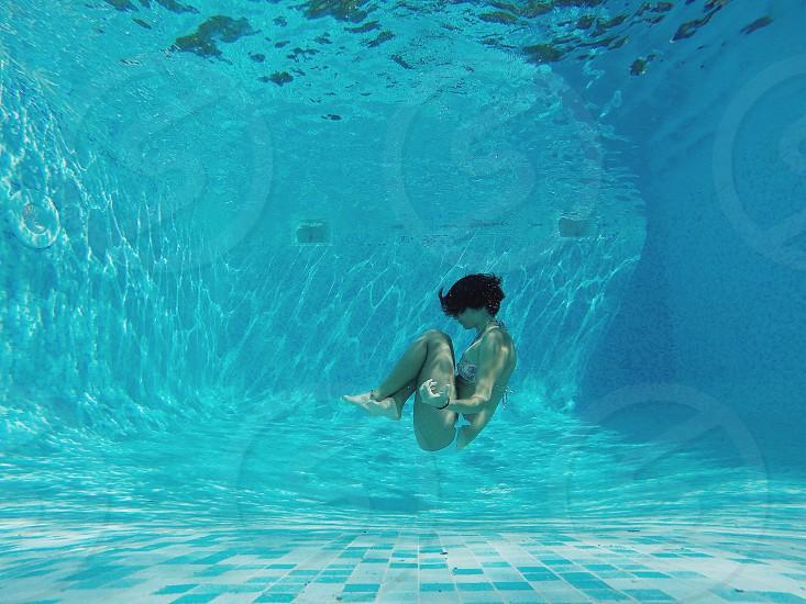 woman in bikini staying under the pool tucking legs during daytime photo