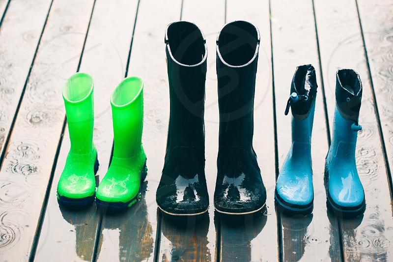 Row of wellies in various sizes standing on a wooden porch while raining photo