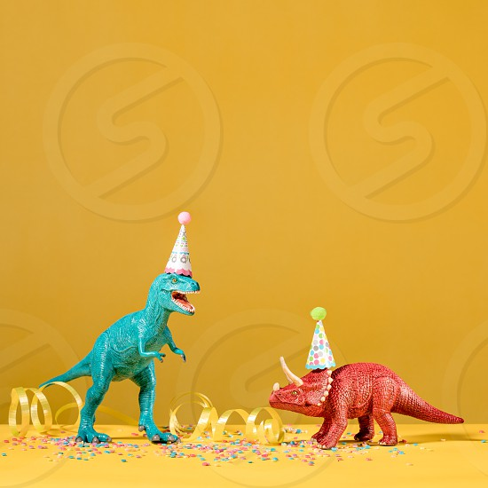 Two dinosaurs with birthday hats partying on a yellow background. photo