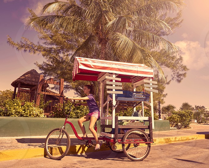 Young girl with caribbean bicycle shop on tricycle of Mexico photo