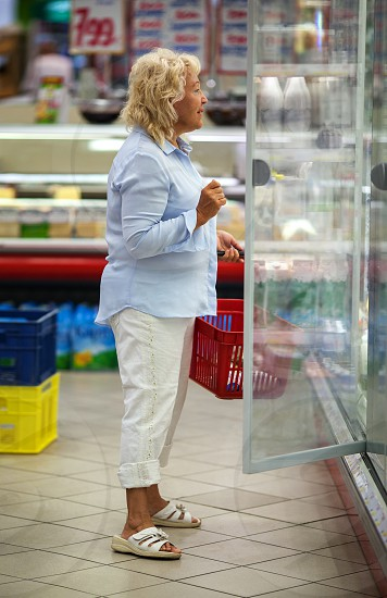Senior woman looking at the dairy in open fridge in the supermarket. Great assortment of products making her think what to choose photo