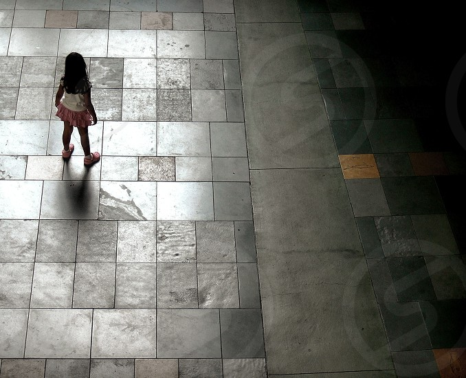Aerial view of a little girl standing on a large tile floor alone photo
