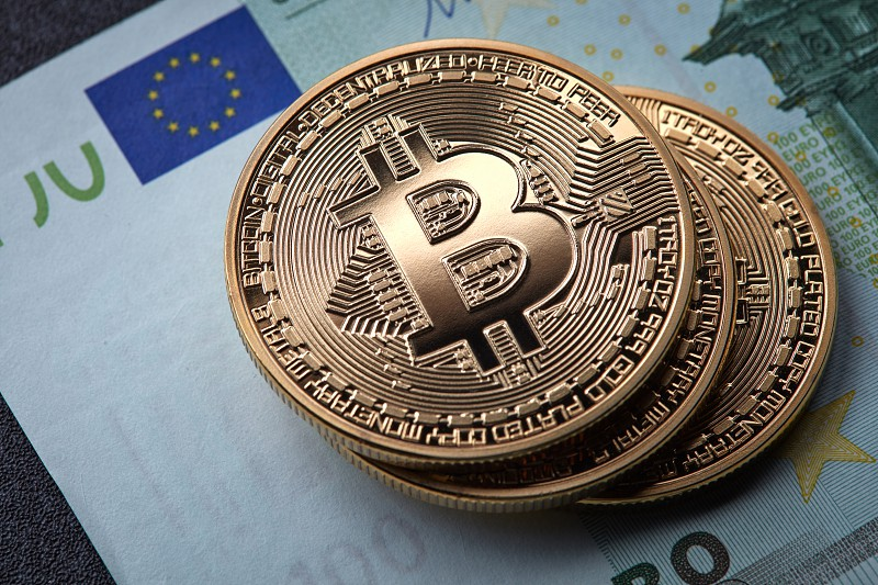 Three gold coins bitcoin stack on paper euro bill. Cryptocurrency business concept. Conceptual image for worldwide cryptocurrency and digital payment system. photo