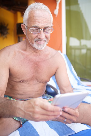 Older man around 60 using tablet computer for reading on vacation photo
