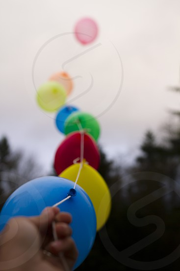 balloons in hand lined up colorful balloons wilderness background photo