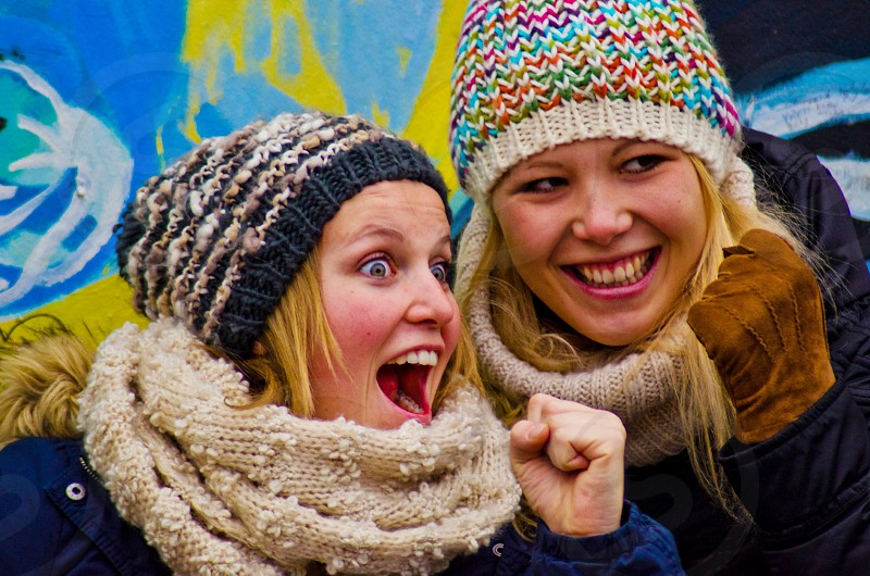 two people wearing a multi-colored beanie photo