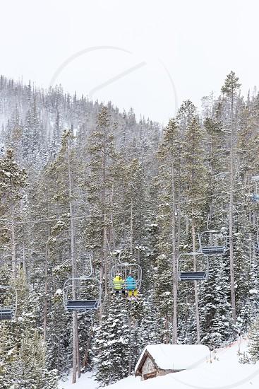 Skiers heading up the mountain on the ski lift at Big Sky Montana photo