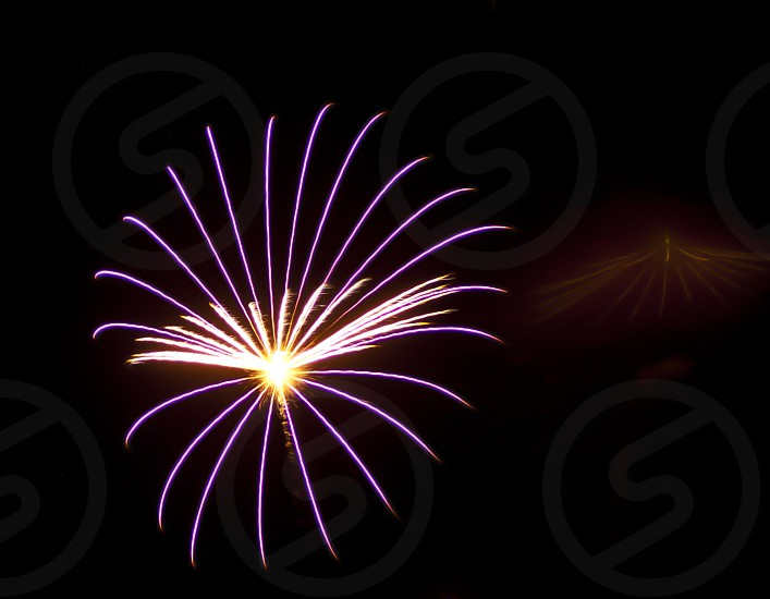 A fireworks display that resembles the spokes of a wheel. photo