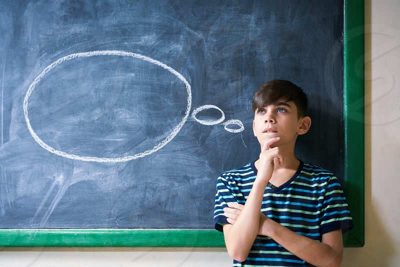 Concepts on blackboard at school. Intelligent and smart hispanic boy in class. Portrait of male kid thinking with hand on chin looking up against cloud drawing on blackboard photo