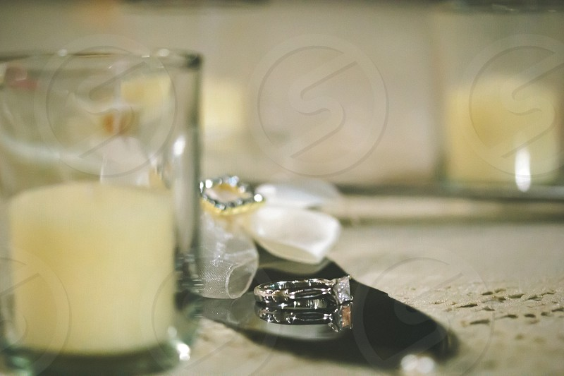 diamond ring beside glass candles  photo