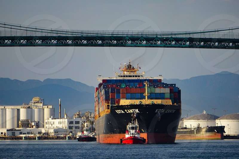 Loaded container ship Kota Cantik escorted by tugboats in main channel of Port of Los Angeles at San Pedro California beneath Vincent Thomas Suspension Bridge mountains in the distance photo