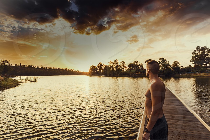 Young man standing without shirt on the jetty looking at the orange light of sunset photo