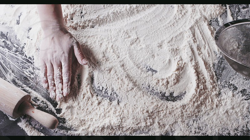 Top view of process of preparation natural dough. Woman's hand move fresh flour on a wooden kitchen table. Slow motion Full HD video 240fps 1080p. Step by step dough preparation. photo