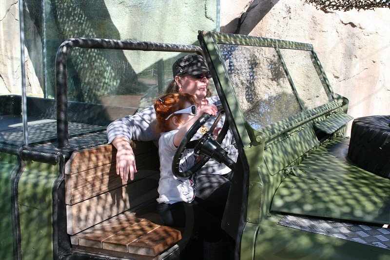 Grandmother and young grand daughter pretending to drive jeep on a safari at the zoo photo