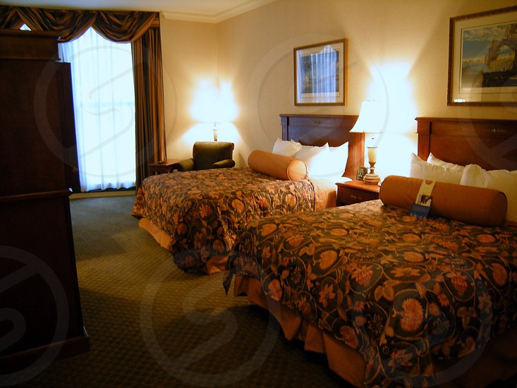 Hotel room with two beds beige walls orange and brown bedspreads photo