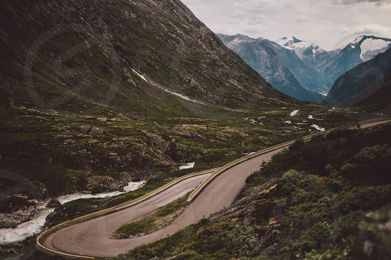 Empty road descending into a valley. Mountains river curvy road.  photo