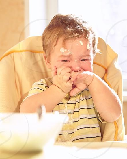 Little boy doesn't want to eat porridge. photo