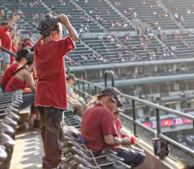 A boy stands and cheers in stands at a baseball game. photo
