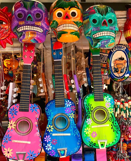 Colorful Mexican masks ukuleles and guitars in an open air market photo