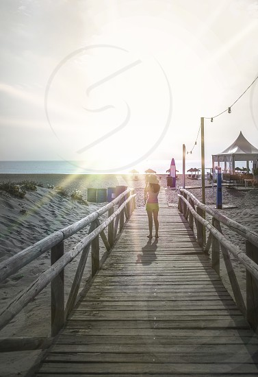 Woman with hat on wooden trail on the beach in the morning. Sunrise photo
