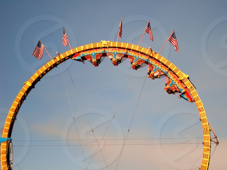 Roller coaster cars upside down on top loop with riders and American flags photo