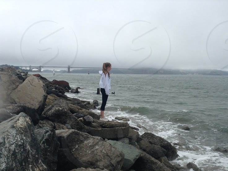 woman wearing white long-sleeved shirt and black capri pants standing on rock formation beside seashore photo