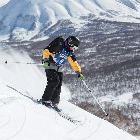"""KAMCHATKA RUSSIA - MARCH 9 2014: Skier rides steep mountains. Competitions freeride skiers and snowboarders """"Kamchatka Freeride Open Cup"""". Far East Russia Kamchatka Peninsula. photo"""