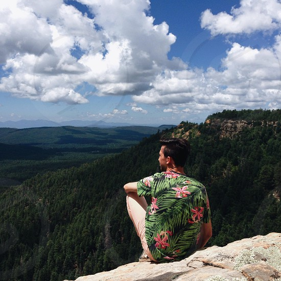 man wearing green and pink floral top seated on rock ledge photo