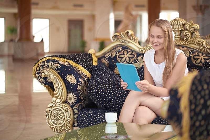 Beautiful woman using a tablet in a hotel lobby sitting enjoying a cup of coffee on an ornate couch smiling as she reads the screen photo