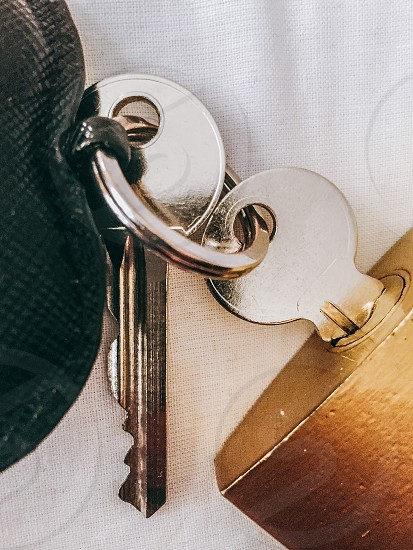 closeup photography of stainless steel key and brass padlock photo