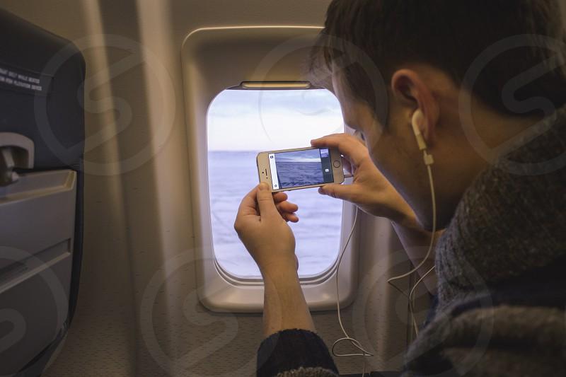 man riding on plane using white earbuds photo