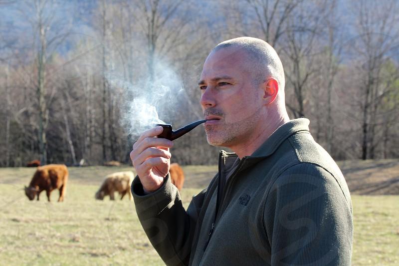 man wearing black zip up jacket using black wooden smoking pipe during daytime photo