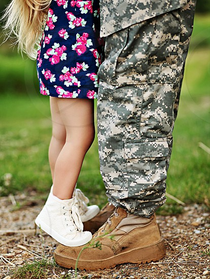 girl standing on the feet of a man in a camouflage military uniform photo