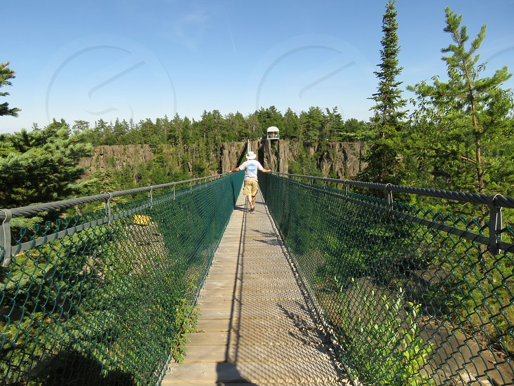 A man in shorts and a hat walks across a suspension bridge for summer fun. Landscape photo. Forest. A canyon.  photo