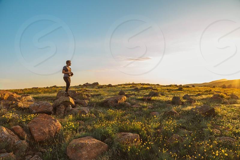 man wearing brown t-shirt standing on rock photo