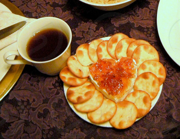 Pepper jelly on cream cheese in shape of a heart surrounded by cracker rounds and served with black coffee on purple tablecloth photo