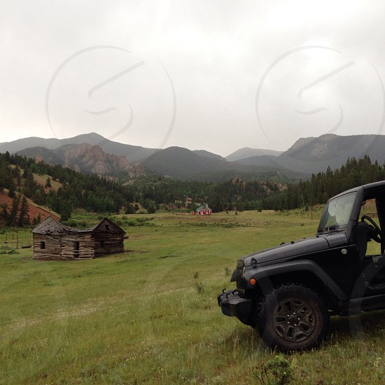 green mountain across green grass field with black parked jeep photo