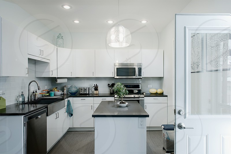white modern kitchen with white cabinets and black counters photo