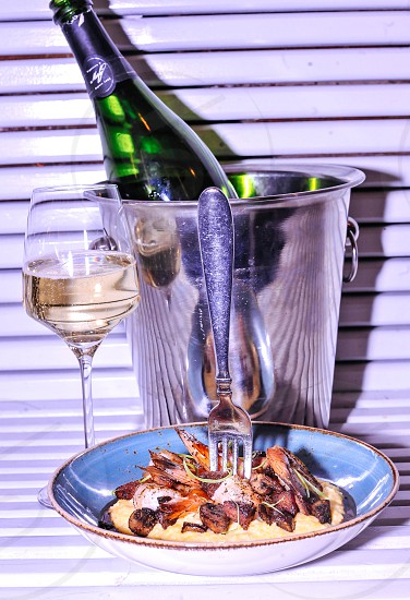 stainless steel fork on prawns with sauce in blue ceramic bowl beside clear long stem wine glass near black labeled bottle in stainless steel bucket photo
