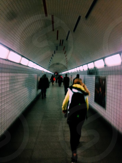 woman wearing yellow and black clothes walking on subway station photo