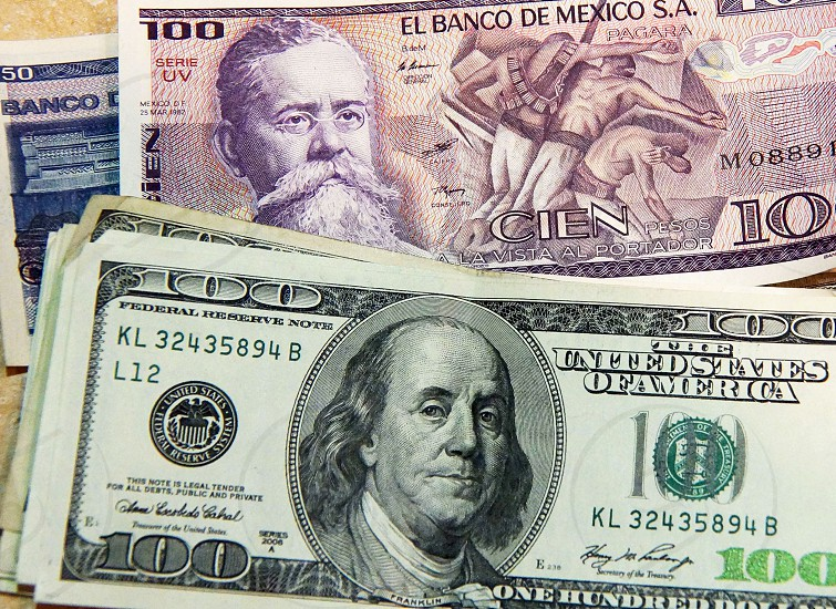 one hundred u s dollar bill on top of a one hundred mexican banknote photo