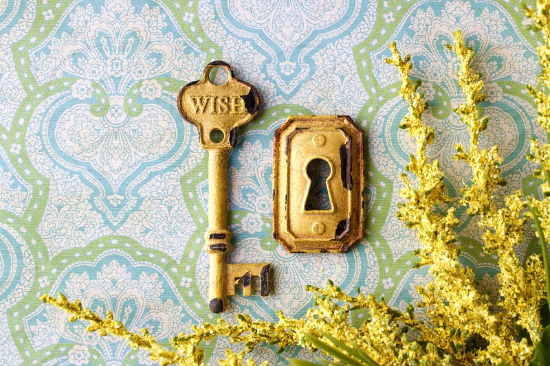 """Flat lay of a rustic yellow vintage key embossed with the word """"WISH"""" keyhole and dried yellow flowers on a light blue and green patterned background in natural light photo"""