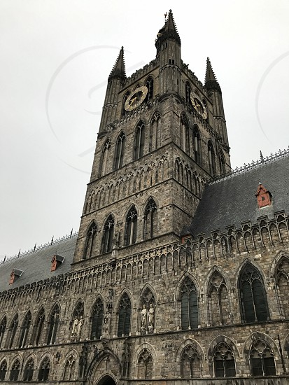 Outdoor day colour vertical portrait Cloth Hall Museum Somme WWI WW1 World War One First World War Ypres Ypres Salient Belgium Europe European gothic style architecture stone sculpture carving masonry building spire tower masonry stone work clock face photo