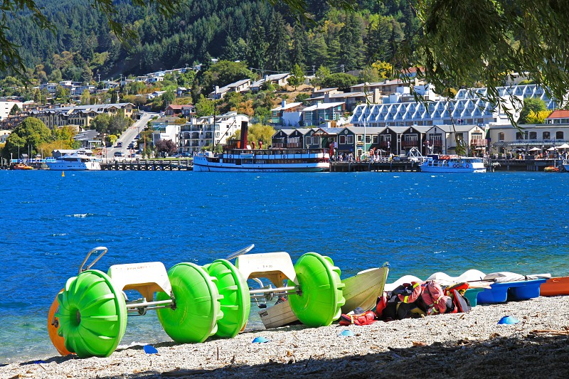Paddle boats line the shoreline of law Wakatipu in Queenstown New Zealand ready for the days fun activities photo